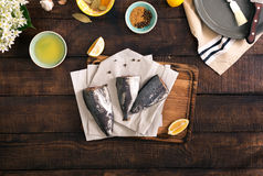 Three fresh raw fish on wooden kitchen board. Three fresh raw fish with lemon and spices for cooking healthy food on wooden kitchen board. Healthy food and diet Stock Images