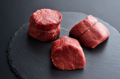 Three fresh raw Prime Black Angus beef steaks on stone backgroun Royalty Free Stock Images