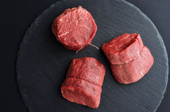 Three fresh raw Prime Black Angus beef steaks on stone backgroun. Three fresh raw Prime Black Angus Tenderloin beef steaks on stone background. Top view Royalty Free Stock Photography