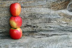 Three fresh red apples on a wooden background Stock Photos