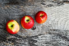 Three fresh red apples on a wooden background Royalty Free Stock Photo