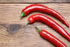 Three Fresh Red Hot Chili Peppers. On The Grunge Rustic Wood Kitchen Table. Background With Copy Space Stock Photography