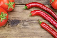 Three Fresh Red Hot Chili Peppers And Tomatoes. On The Rustic Wood Kitchen Table. Background With Copy Space. Ingredients for Soup, Salad, Paste Stock Image