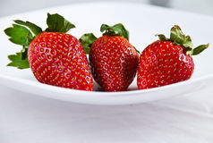Three fresh red strawberries. On white plate and isolating background Stock Images