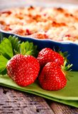 Three fresh red strawberries in front of fruit cake on green towel royalty free stock photography