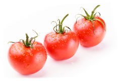 Three fresh red tomatoes. In perspective in a diagonal line on a white background Stock Photo