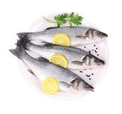 Three fresh seabass with lemon slices. Royalty Free Stock Photos