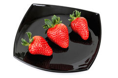 Three fresh strawberries on black saucer Royalty Free Stock Image