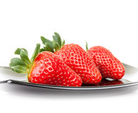 Three fresh strawberries on glass saucer Royalty Free Stock Images