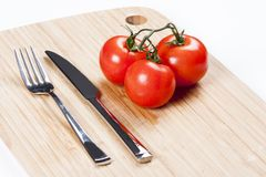 Red fresh tomatoes on chopping board Stock Image