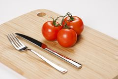 Red fresh tomatoes on chopping board Stock Photo