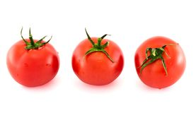 Three fresh tomatos covered with water drops isolated. Three fresh tomatos in different foreshortenings covered with water drops isolated over white background Royalty Free Stock Image