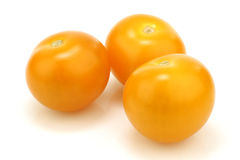 Three fresh yellow cherry tomatoes Royalty Free Stock Photography