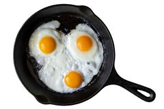 Three fried eggs in cast iron frying pan isolated on white from royalty free stock images