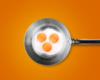 Three Fried eggs in a frying pan. On orange background Stock Photo