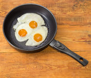 Three fried eggs in the frying pan on wooden planks Royalty Free Stock Photos