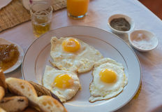 Three fried eggs on white plate for breakfast Royalty Free Stock Photos