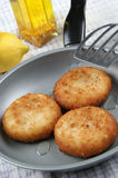 Three fried fish cakes in a pan Royalty Free Stock Photo