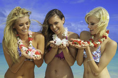 Three friend in bikinis with flowers Royalty Free Stock Photo