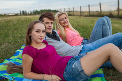 Three friend relaxing on colorful blanket in park. Summertime. Stock Image