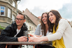Three friend socializing at restaurant table Stock Image