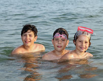 Three friendly brothers swimming in the ocean during summer vaca Royalty Free Stock Photos