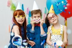 Three friendly children in festive cone caps and big eyewear, stand in decorative room with balloons, have fun together. As celebrate birthday look with happy Royalty Free Stock Image