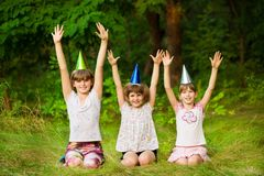 Three friendly children in festive cone caps, sit on grass, have fun together as celebrate birthday royalty free stock image
