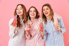 Three friendly women with good mood in colorful striped pyjamas. Smiling and drinking cold soda or juice from glass bottles during fun girl party isolated over royalty free stock image