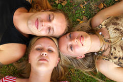Three friends. Lying on the grass Stock Photography