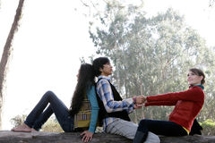 Three friends. A view of three friends, two women and a man, enjoying being together outdoors Royalty Free Stock Photography
