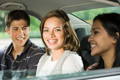 Three friends in the back of a car Stock Photos