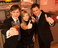Three friends in a bar. Showing thumbs up Royalty Free Stock Photos