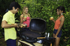 Three friends at a barbecue Royalty Free Stock Image