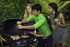 Three friends at a barbecue Stock Photos
