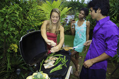 Three friends at a barbecue Stock Photo