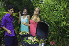 Three friends at a barbecue Stock Photography