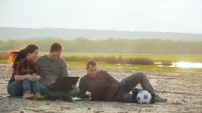 Three friends on the beach with laptops slow motion video. Three friends on the sandy beach working with laptop and laughing communicate with each other two men stock footage
