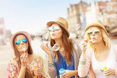 Three friends blowing soap bubbles Royalty Free Stock Photography