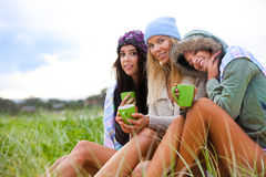 Three Friends Bundled Up With Coffee Cups. Portrait of three attractive young women smiling and sitting together in the grass at the coast.  They are bundled up Stock Photos