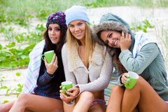 Three Friends Bundled Up With Coffee Cups at the B. Portrait of three attractive young women smiling and sitting together on a beach.  They are bundled up Stock Images