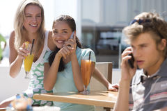 Three friends in cafe outdoors, young man and young woman using mobile phones Royalty Free Stock Photo