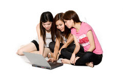 Three friends chatting online. Three young friends chatting online on a notebook computer sitting on the floor stock image