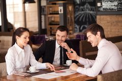 Three friends discuss graph lying on table at cafe. Stock Image
