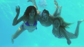 Three friends diving into swimming pool and waving