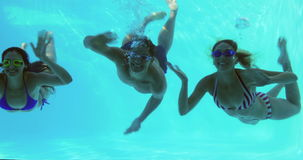 Three friends diving into swimming pool and waving Stock Photo