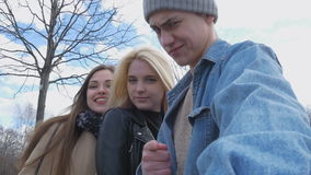 Three friends, do selfie for a walk in the park. Blonde, brunette and a young man. Have fun and enjoy life. A beautiful sunny day stock video