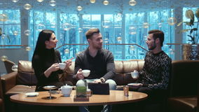 Three friends drink tea in lobby of hotel stock video