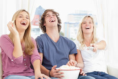 Three friends eating popcorn while laughing Royalty Free Stock Image