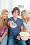Three friends eating popcorn together Royalty Free Stock Photography